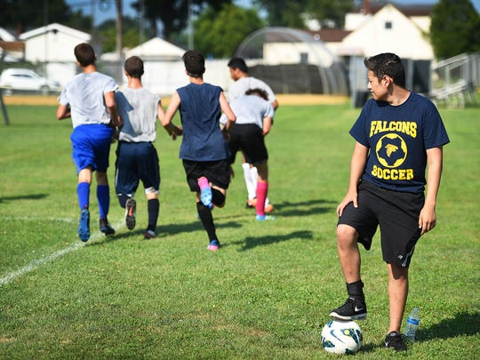 Saddle Brook HS junior David Guerra, who was undergoing serious leukemia treatments, looks toward teammates running as he is back on the field to warm up by his own    at Carmelo Virga Field in Saddle Brook on July 19th, 2017.