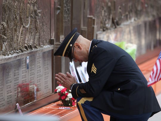"""Army Reserve Sgt. Edwin Morales of Brooklyn on Monday outside """"Ten House,"""" a firehouse that was destroyed in the 9/11 attacks. Morales is praying beside the name of his cousin, Ruben Correa, a New York City firefighter who was killed on Sept. 11, 2001."""