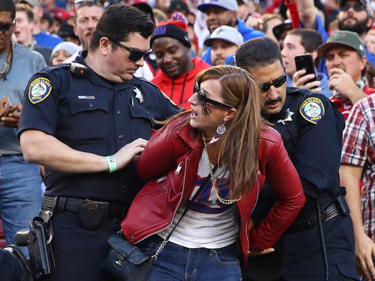 A fan fights with police and is detained during the