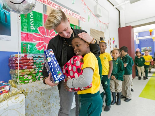 Student Shawdon Green receives a holiday gift and a hug from phys-ed teacher Jennifer Olawski (left) at the Community Charter School in Paterson on Monday, December 18, 2017.