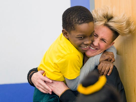Shawdon Green gives a flying hug to phys-ed teacher Jennifer Olawski, whose GoFundMe page raised money to buy a gift for every student at the Community Charter School in Paterson.