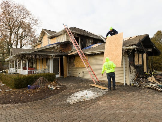 Contractors secure the remnants of the home belonging