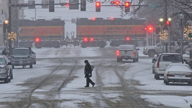 A pedestrian crosses a snow covered street in downtown Bismarck, N.D., on Monday, Dec. 4, 2017. Blizzard warnings were posted for northwest Minnesota, southeast North Dakota and northeast South Dakota where winds were expected to whip up snow and create white-out conditions.