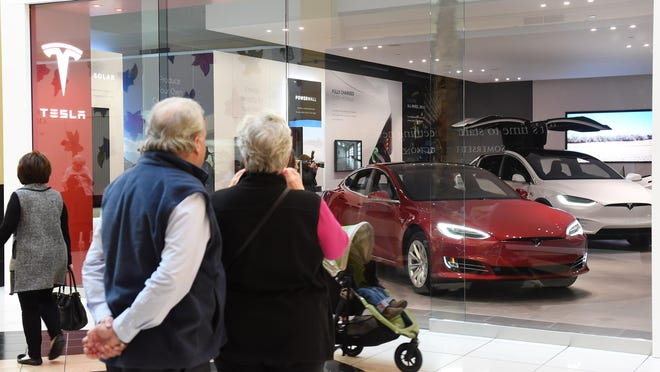 Bob and Sherrie Bradley of London, Ont. pause to take a photo to send to their son, who they say is a car nut, while passing by the Tesla gallery at the Somerset Collection in Troy on Thursday.