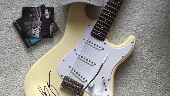 A hat, CD and guitar autographed by Luke Bryan will