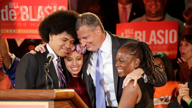New York Democratic mayoral candidate Bill de Blasio embraces his son Dante, left, daughter Chiara, second left, and wife Chirlane McCray after polls closed in the city's primary election in New York. De Blasio and his wife settled in the Park Slope neighborhood of the Brooklyn borough of New York largely because they felt that their interracial relationship would be accepted there, the mayor-elect has said.