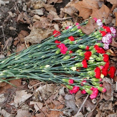 A bouquet of flowers placed below a sign marking the