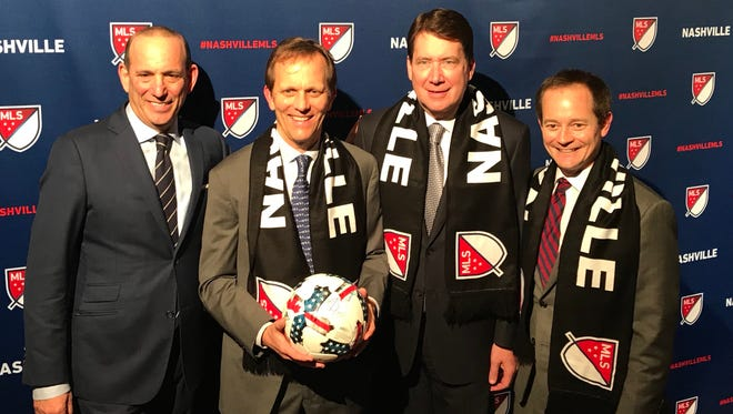 MLS Commissioner Don Garber (far left) poses for a photo opportunity in the media mixed zone Wednesday at the Country Music Hall of Fame for the introduction of Nashville as the 25th MLS franchise.