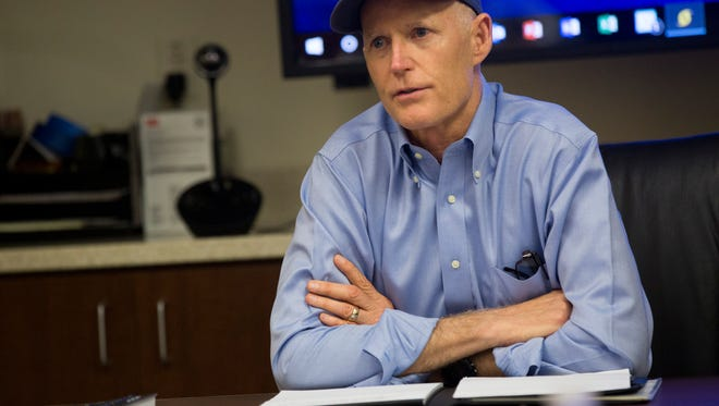 Florida Gov. Rick Scott speaks with local response officials while also holding a press conference to discuss impending Hurricane Irma during a quick stop at the Collier County Emergency Operations Center Wednesday, September 6, 2017 in Naples.