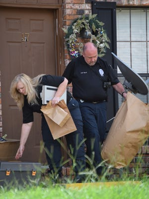 Hattiesburg police crime scene investigators Denise Ruple and Jeff Byrd carry bags of evidence collected at the scene where a baby was found dead Monday.