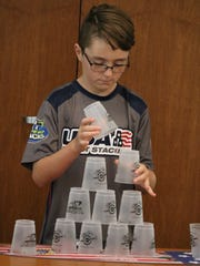"Gold medalist sport stacker Dominic Pappagallo, 11, practices a complete ""cycle"" stack during his visit to the Marblehead Peninsula Branch Library on Saturday."