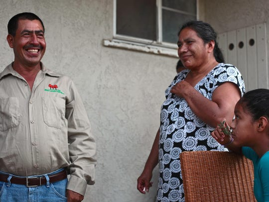 Gonsalo Solis, his wife Maria Gonsalez and their daughter Christina Gonsalez stand outside their new home in Desert Hot Springs. The family's trailer home was destroyed in a fire last month.