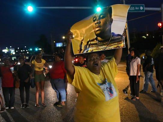 Sharon Cowan chants as she marches Tuesday, Aug. 9,