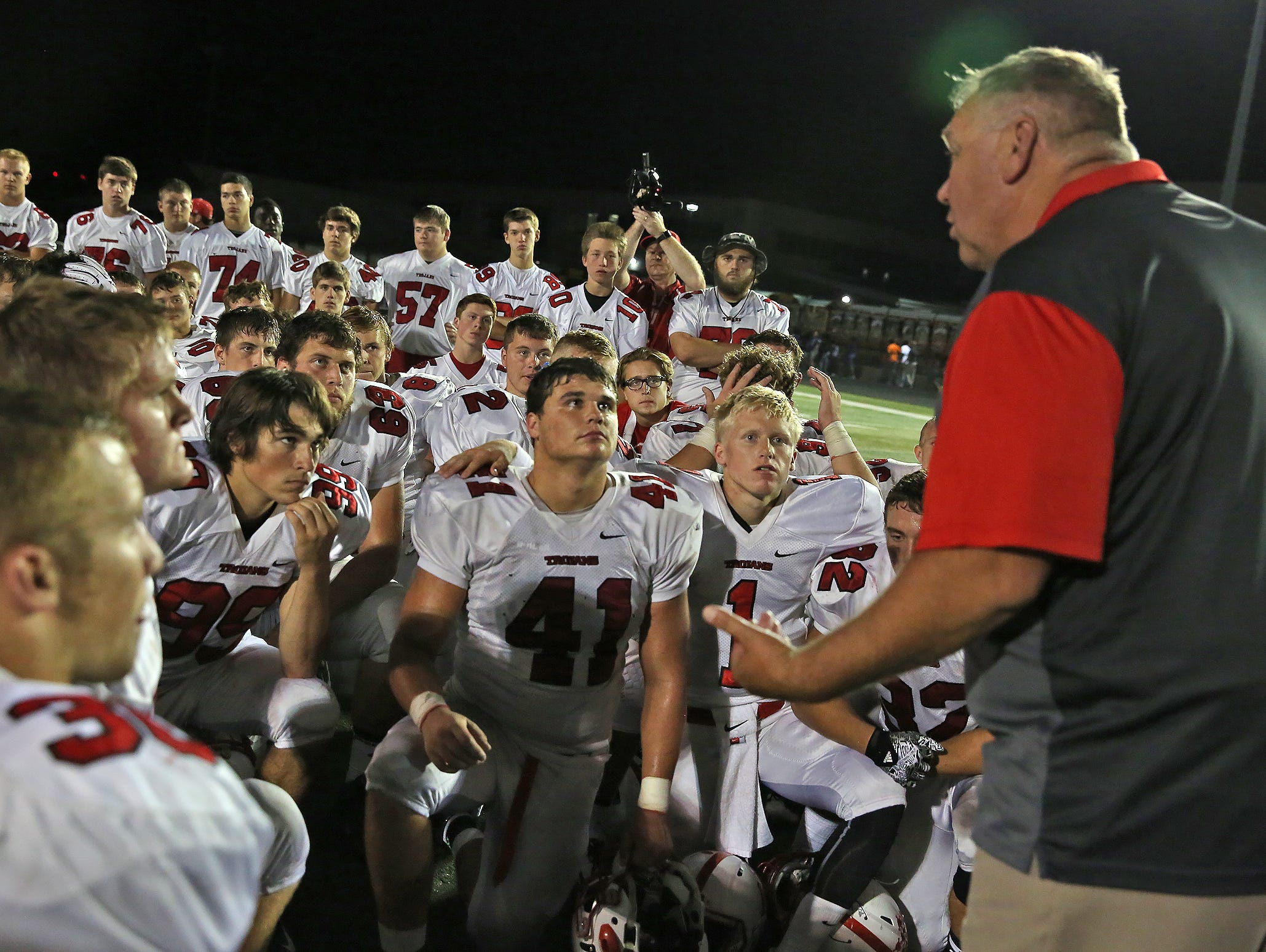 Center Grove head coach Eric Moore talks to his team after their victory football game at Lawrence Central, Friday, September 25, 2015. Center Grove won 44-26.