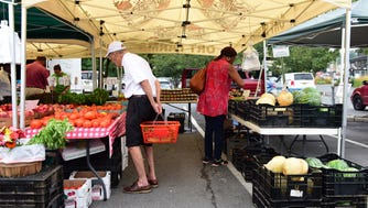 Shoppers at Ort Farms tent. The weakly Farmer's Market in downtown Millburn brings families and restaurateurs together to buy farm fresh foods.