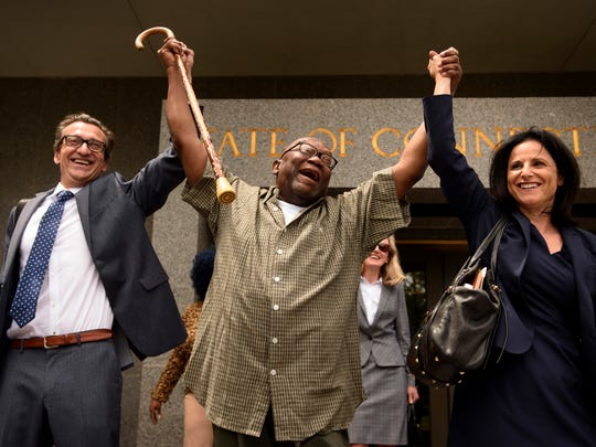 "Shouting ""Freedom,"" Alfred Swinton, middle, walks out of the Connecticut Supreme Court  in Hartford, Conn.,  with Innocence Project lawyers Chris Fabricant, left, and Vanessa Potkin after a Superior Court judge approved a new trial in his conviction in the 1991 murder of Carla Terry. After serving 18 years, Swinton, 68, was released on a promise to appear in court."