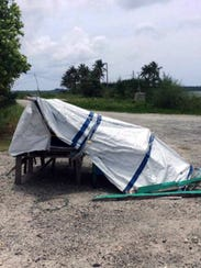 A tarp held up with posts is a shelter for one of 34