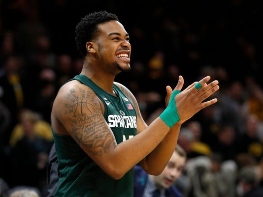 Michigan State forward Nick Ward celebrates in the bench area at the end of the team's NCAA college basketball game against Iowa, Tuesday, Feb. 6, 2018, in Iowa City, Iowa. Michigan State won 96-93. (AP Photo/Charlie Neibergall)