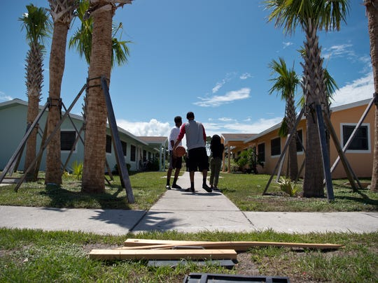 Jontae Richardson, 17, (from left) Gary Coleman, 18, and his sister spend time outside their home Aug. 17, 2016, on North 31st Street in Fort Pierce.