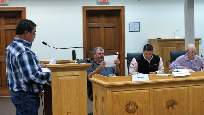 From left, CAPE Director Anthony Gutierrez presents as CAPE members Aaron Sera and Marcos Mendiola examine documents.