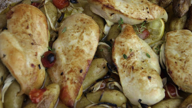Baked chicken is served with potatoes.