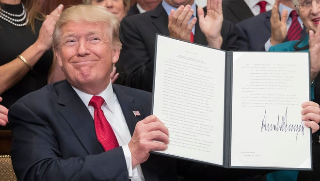 President Trump holds up an executive order on health care after signing it during a ceremony in the Roosevelt Room of the White House on Thursday. Hours later, he announced the federal government would no longer cover cost-sharing subsidies.