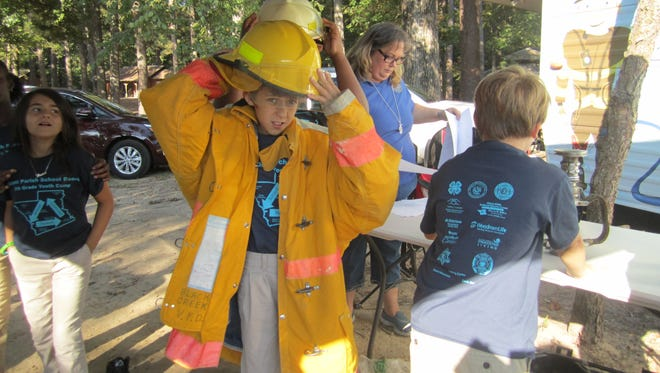 Maximus Kinler, a 10-year-old Colfax Elementary School fifth-grader, tries on some firefighter gear Thursday at Camp Grant Walker.