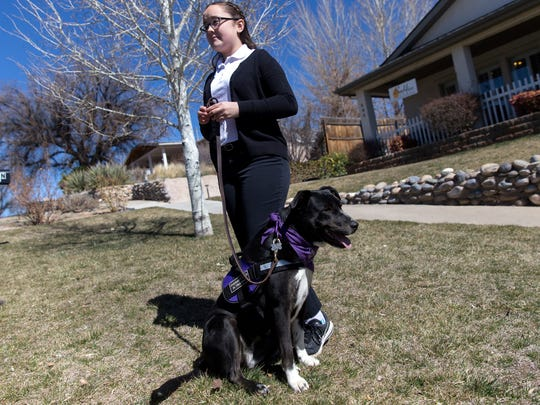 In this Tuesday, March 7, 2007 photo, Alexandra Burnham waits with her dog Lucy before visiting residents, at the Beehive Homes in Farmington, N.M.