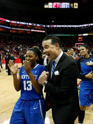 Kentucky's coach Matthew Mitchell and Bria Goss celebrate after the Cats took down the 7th ranked Cardinals 77 - 68. Dec. 7, 2014