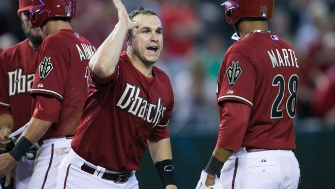 Miguel Montero and teammates celebrate after Alfredo Marte had a walkoff fielder's choice at Chase Field in Phoenix on Sunday, August 3, 2014.
