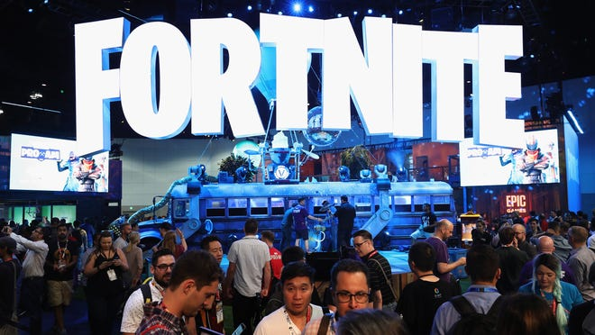 Game enthusiasts and industry personnel visit the Fortnite exhibit at the Electronic Entertainment Expo E3 at the Los Angeles Convention Center June 12, 2018, in Los Angeles.
