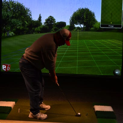 Bob Shaw, of Vestal, putts into the golf simulator