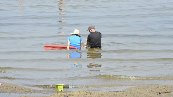 A couple sits in the water at Blanchard Beach at Oakledge Park in Burlington on Sunday, July 1, 2018. he temperature approached 90 degrees by 11 a.m., with the National Weather Service issuing an Excessive Heat Warning in the Champlain Valley through 10 p.m. Monday.The forecast calls for the temperature to top 90 degrees through Thursday.