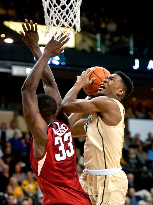 Wake Forest's Bryant Crawford looks for a shot as Arkansas' Moses Kingsley defends during an NCAA college basketball game Friday, Dec. 4, 2015, in Winston-Salem, N.C. (Lauren CarrollWinston-Salem Journal via AP)