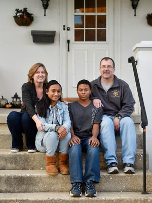 Barbara and Dave Michaels sit for a portrait with Nisheah Stambaugh, 15, center left, and Robert Oliver, 16, center right, on their York porch. The Michaels became mentors to the two William Penn students last year as part of the school's freshman mentorship program, and continue to remain active in their lives.