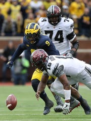 Michigan's Mike McCray and Ohio State's J.T. Barrett go after a fumble in the second quarter Saturday, Nov. 25, 2017 at Michigan Stadium.
