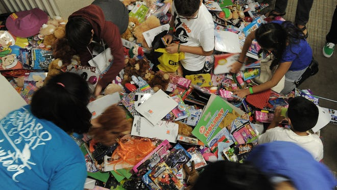 Children sort through hundreds of stuffed animals and other items at Operation Snowflake, for military and veteran families. The Ventura County Military Collaborative gave over 300 children free toys and other goodies.