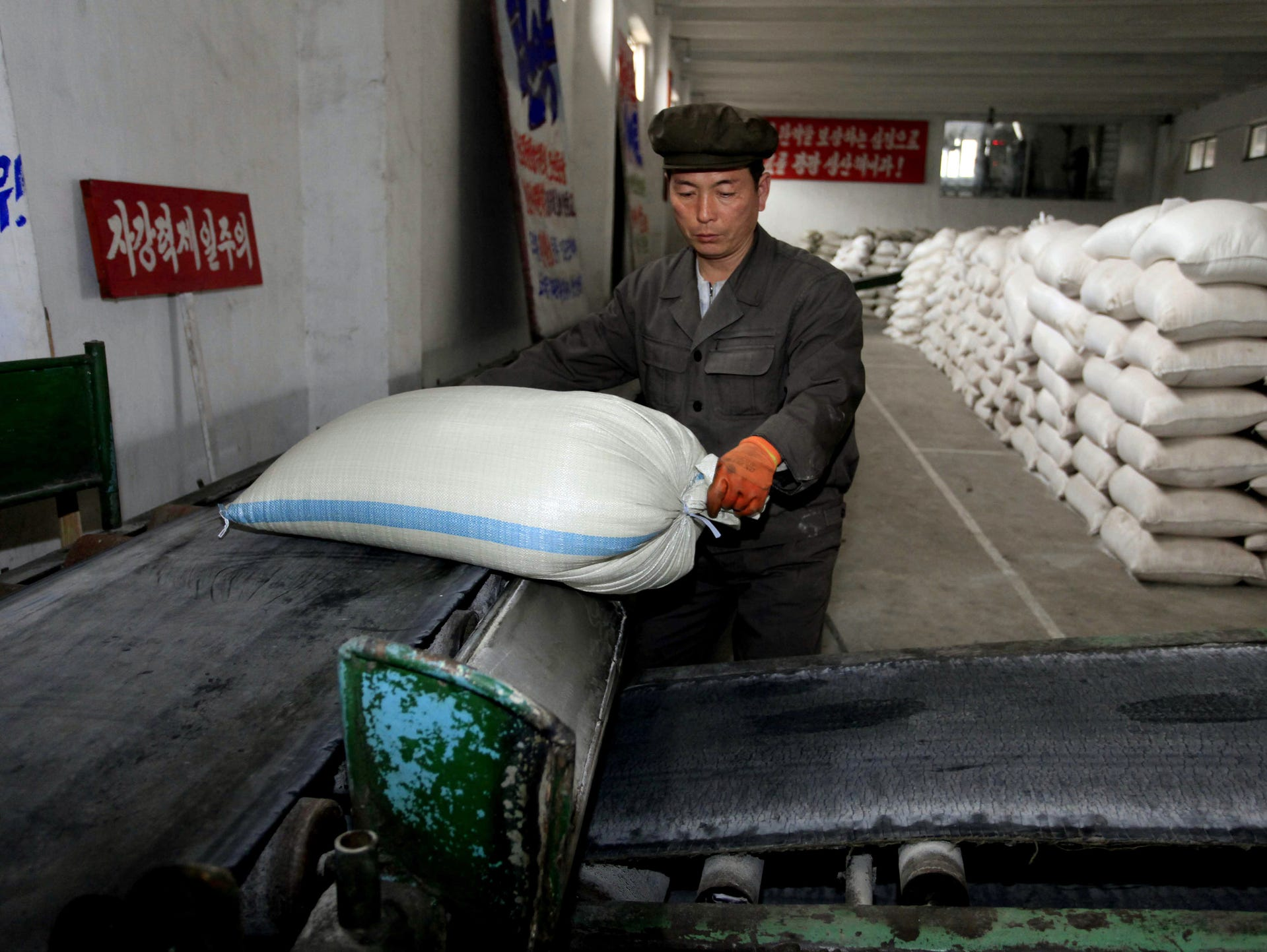 firenewsfeed a worker unloads a bag of fertilizer from a conveyer belt at hungnam fertilizer complex in hungnam south hamgyong province 13 2016