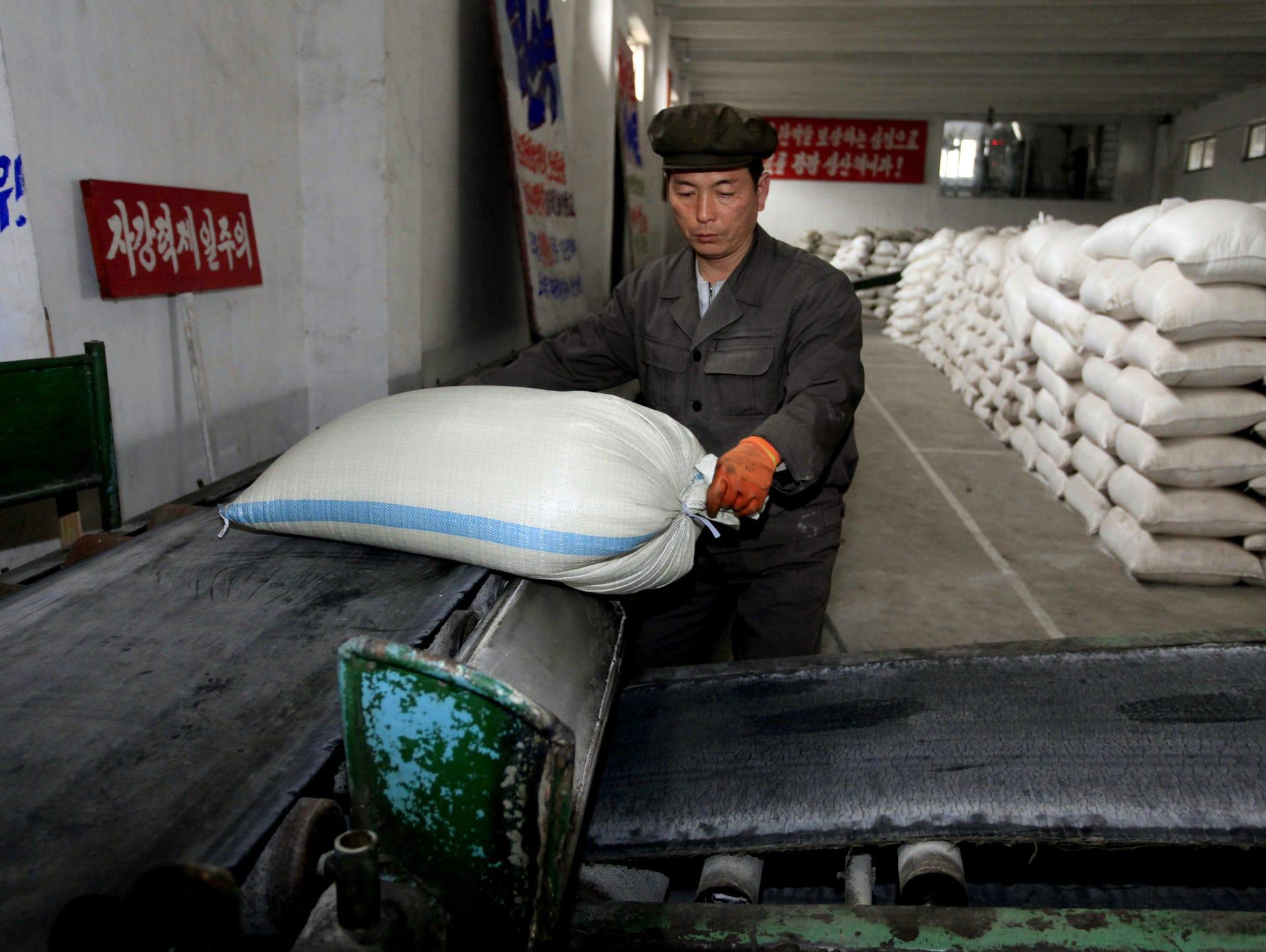 a worker unloads a bag of fertilizer from a conveyer belt at hungnam fertilizer complex in hungnam south hamgyong province 13 2016
