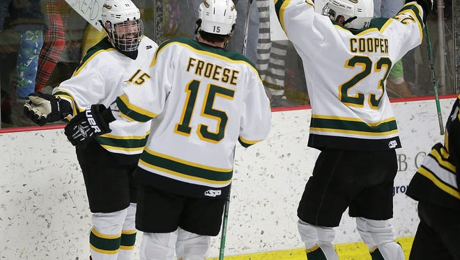 At left, St. Norbert College forward Michael Hill (11) is all smiles after scoring a goal against Adrian College in the first period during a game on Jan. 22 at the Cornerstone Community Center in Ashwaubenon. Also pictured are sophomore Tanner Froese (15) and senior captain Erik Cooper (23).