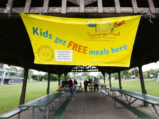 A banner whips in the wind Wednesday at Brand Park, alerting children free meals are being offered.