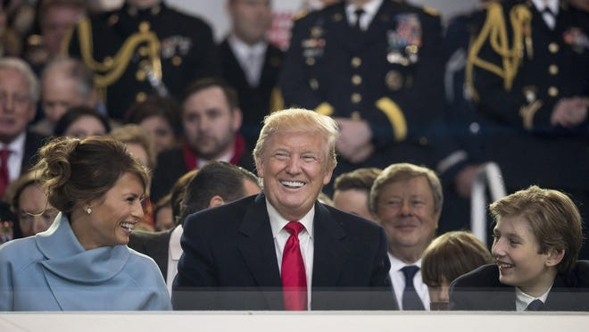 President Donald Trump shares a laugh with First Lady Melania Trump and son Barron Trump as they sit in the reviewing stand during Trump's inaugural parade on Pennsylvania Ave. last Friday.