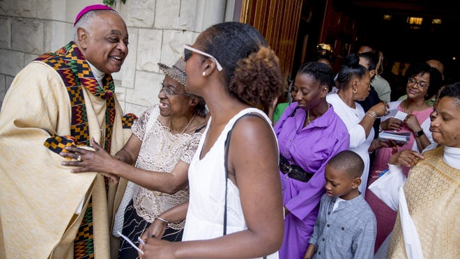 "FILE - In this Sunday, June 2, 2019 file photo, Archbishop of Washington Wilton Gregory, left, greets parishioners following Mass at St. Augustine Church in Washington. In June 2020, Gregory, the first African-American in charge of the Archdiocese of Washington, joined with eight fellow bishops from his region to acknowledge the church's ""sins and failings†in regard to racial justice. ""Prayer and dialogue, alone, are not enough. We must act to bring about true change,†the bishops said, calling for more racial equality in health care, education, housing and criminal justice."