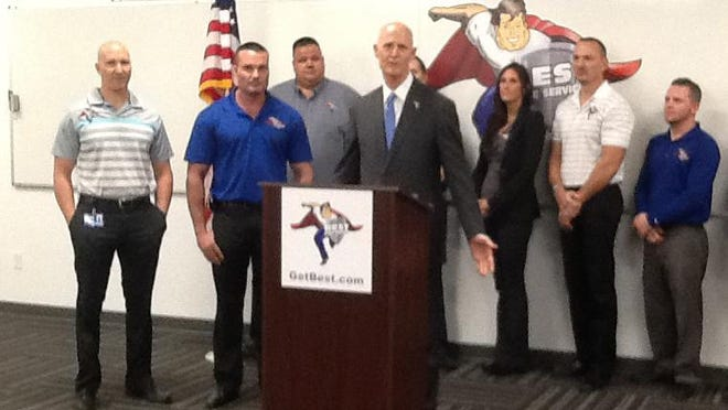 Gov. Rick Scott celebrates job creation at Best Home Services in North Naples on Monday. At left are the company's owners, Chadd and Keegan Hodges.