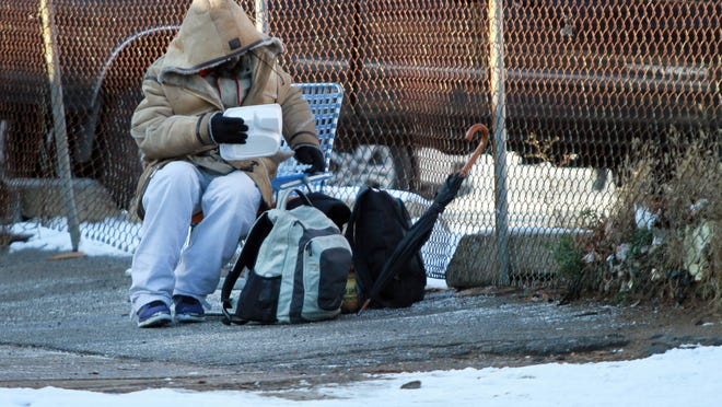 A homeless man sits along East Front Street in the frigid temperatures near the Sunday Breakfast Mission on Wednesday afternoon.