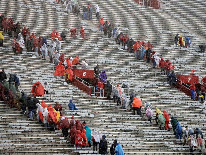 Fans leave the stadium during a weather delay in the