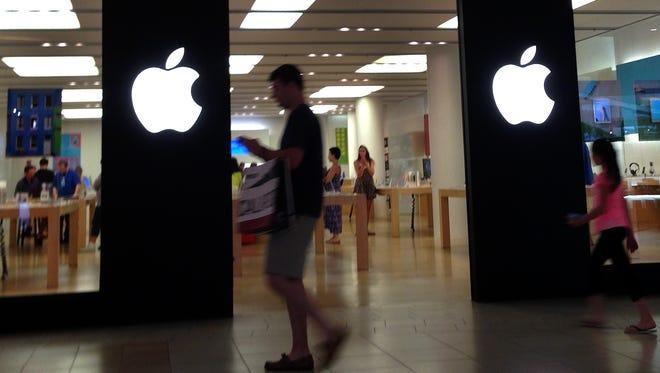A shopper walks by an Apple store in Peabody, Mass.