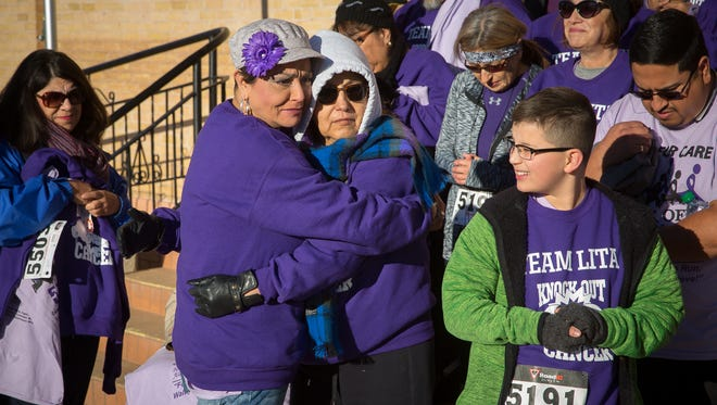 Sonja Portillo, center left, hugs her sister Lita Lujan, who is battling pancreatic cancer, during Cancer Aid Resource & Education's Race for Care event in Mesilla. According to Portillo up to 69 people raced on behalf of Lujan to raise money for CARE.