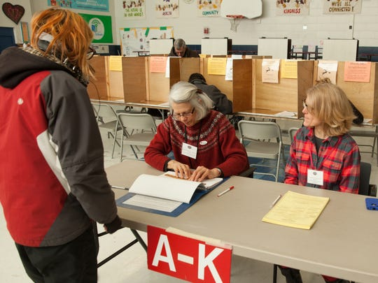 Kayla Billings checks in with election officials 'Kit' Andrews and Amanda Hannaford at Lawrence Barnes Elementary School to vote in Ward 3.