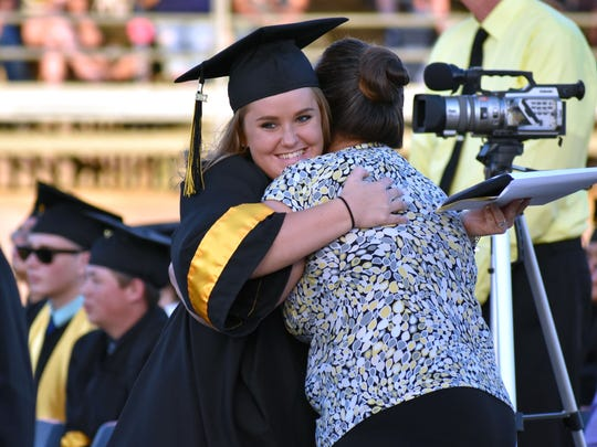 Megan Cullers hugs a teacher after receiving her diploma.